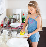 Girl doing dishes at kitchen Stock Photography