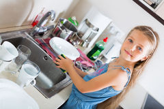 Girl doing dishes at kitchen Royalty Free Stock Image