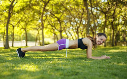 Girl doing elbow plank pose outdoors stock photo