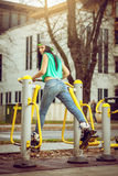 Girl doing exercise in public open air gym Royalty Free Stock Photo