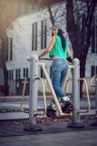 Girl doing exercise in public open air gym Stock Photos