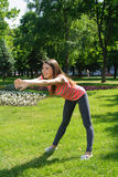 Girl doing exercise tilts forward outdoors in the park Royalty Free Stock Photo