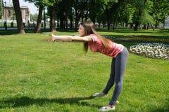 Girl doing exercise tilts forward outside Stock Image