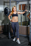 Girl doing exercises with barbell in gym Stock Image