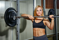 Girl doing exercises with barbell in gym Stock Photos