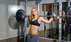 Girl doing exercises with barbell in gym Royalty Free Stock Photography