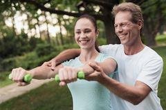 Girl doing exercises with dumbbells in the park. A man helps her. They are smiling Royalty Free Stock Photos