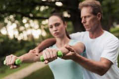 Girl doing exercises with dumbbells in the park. A man helps her. They are smiling Royalty Free Stock Photo