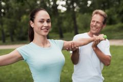 Girl doing exercises with dumbbells in the park. A man helps her. They are smiling Stock Photo