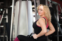 Girl doing exercises for muscles of back on training apparatus Royalty Free Stock Photography