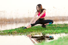 Girl doing exercises on near lake Stock Images