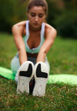 Girl doing exercises in park, selective focus on shoes Royalty Free Stock Image