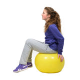Girl doing exersises on the yellow ball Royalty Free Stock Image