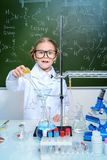 Girl doing experiments. Surprised little girl doing experiments in the laboratory. Science and education stock photos