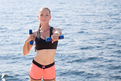 Girl doing fitness exercises with dumbbells royalty free stock photo