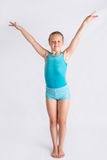 Girl doing gymast salute. Tween girl standing on white backdrop doing a full body gymnastics salute Royalty Free Stock Photos