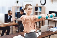 A girl is doing gymnastic exercises at work. stock photography