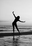 Girl doing gymnastics on the beach at sunset Stock Photos