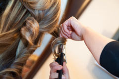 Girl doing hairstyle curling Royalty Free Stock Image