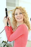 Girl doing hairstyle with flat iron. Young blonde girl doing hairstyle with flat iron - young woman in home Stock Photo