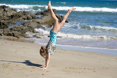Girl doing hand stand. Girl attempting a hand stand at the sea shore Stock Images