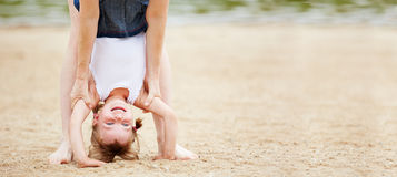 Girl doing handstand on beach. Happy girl doing handstand on beach with help of her mother Royalty Free Stock Images