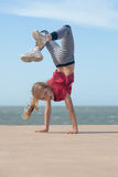 Girl doing handstand. Happy little girl doing handstand by the ocean Royalty Free Stock Image