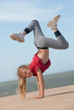Girl doing handstand. Happy little girl doing handstand by the ocean Stock Photography