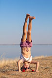 Girl doing head stand on the beach Royalty Free Stock Image