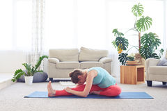 Girl doing head-to-knee forward bend pose Stock Photography