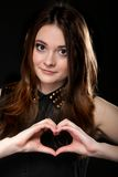 Girl doing heart shape love symbol with her hands. Beautiful young woman over black background doing a heart shape love symbol with her hands. Concept of royalty free stock image