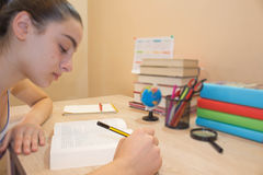 Girl doing her homework. School books on desk, education concept. Young Girl doing lessons at home Royalty Free Stock Photography
