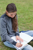 Girl doing her homework while sitting on the grass Stock Image
