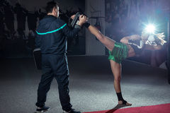 Girl doing high kick in kick boxing. Young adult women doing high kick during kickboxing training exercise Royalty Free Stock Images