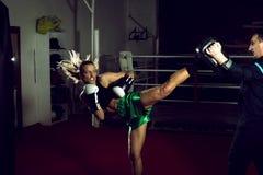 Girl doing high kick in kick boxing Stock Images