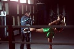 Girl doing high kick in kick boxing. Young adult women doing high kick during kickboxing training exercise Stock Photos