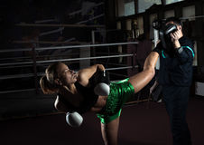 Girl doing high kick in kick boxing. Young adult women doing high kick during kickboxing training exercise Stock Images