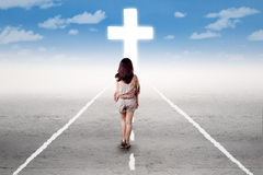 Girl doing a holy trip to the cross Stock Photography