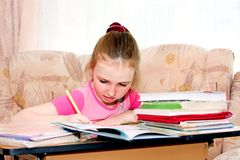 Girl doing homework. Sitting at desk Stock Photo