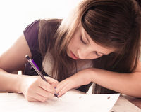 Girl Doing Homework. Cute teenage girl doing homework Royalty Free Stock Photo