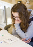 Girl doing homework. A girl reading an English language exercise book, learning at home Stock Image