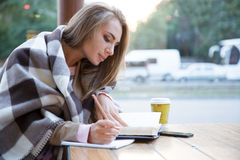 Girl doing homework in cafe. Portrait of a charming girl doing homework in cafe Stock Image