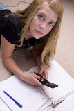 Girl doing homework with cell phone. A girl texting on her phone while she is doing her homework Stock Photos