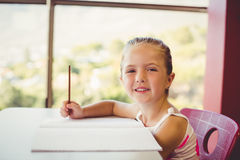 Girl doing homework in classroom Royalty Free Stock Photo