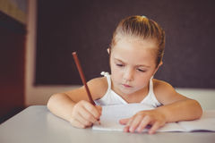 Girl doing homework in classroom Royalty Free Stock Image