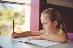 Girl doing homework in classroom Royalty Free Stock Photography