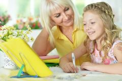 Girl doing homework. Cute girl and doing homework with her mother Royalty Free Stock Images