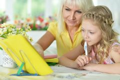 Girl doing homework. Cute girl and doing homework with her mother Stock Photography