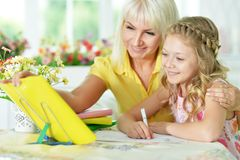 Girl doing homework. Cute girl and doing homework with her mother Royalty Free Stock Photography