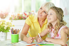 Girl doing homework. Cute girl and doing homework with her mother Stock Images